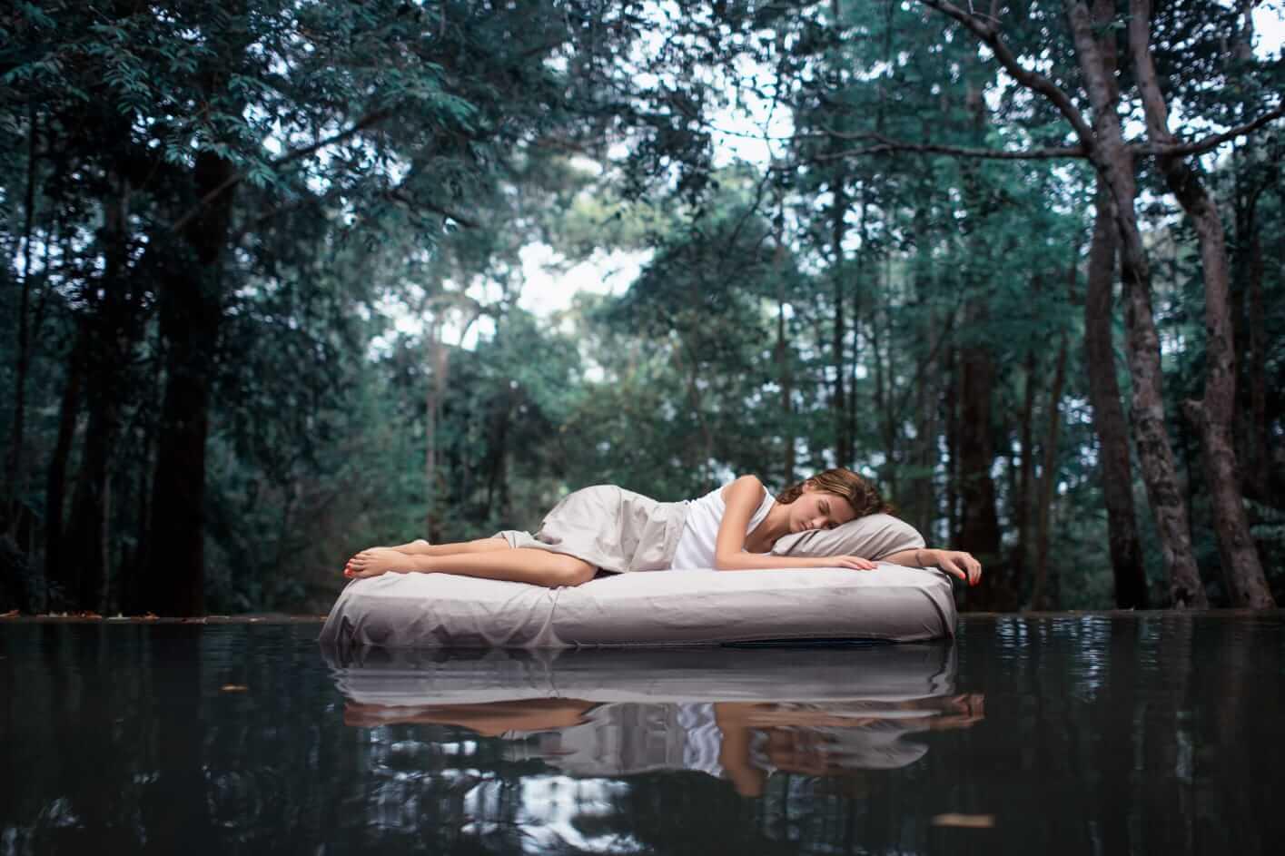 Frau entspannt sich auf einer Luftmatratze auf dem Wasser im Wald