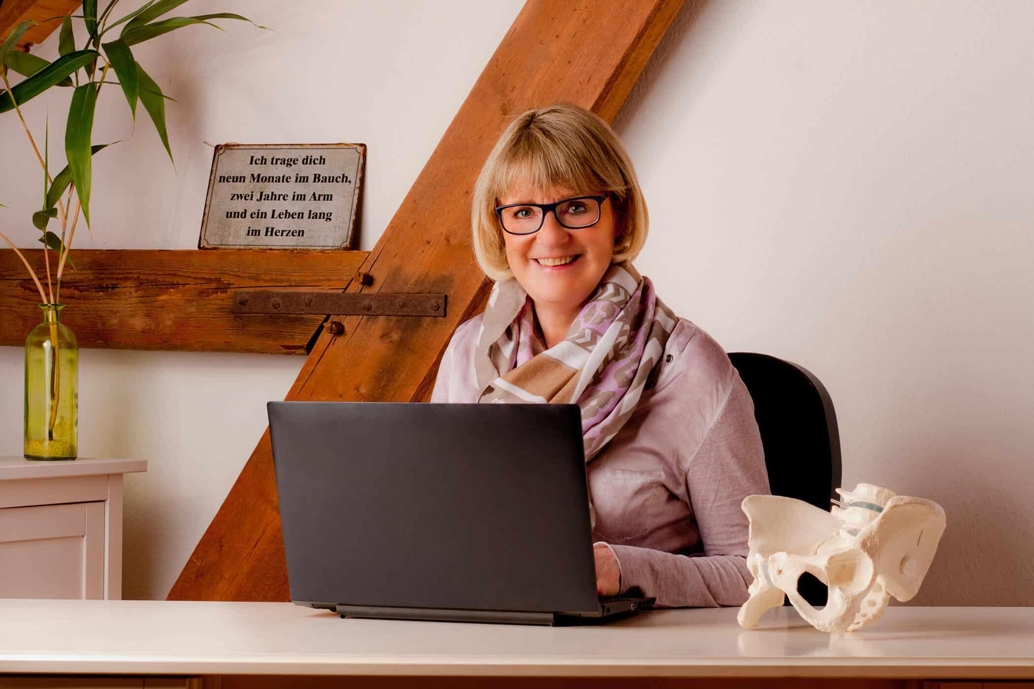 Petra Kleist sitzt vor dem Laptop mit einem Becken zur Veranschaulichung Ihrer Geburtsvorbereitungsübungen